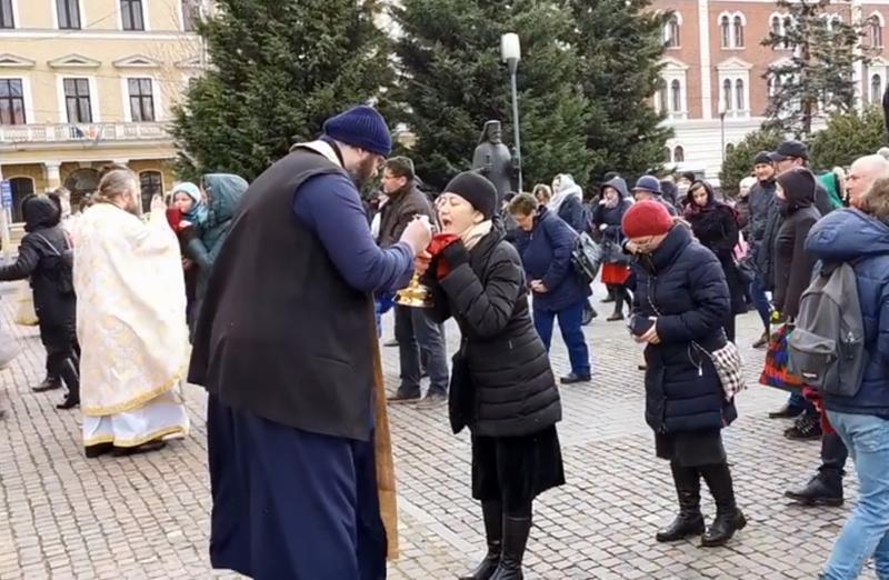 VIDEO Cluj Napoca: Mai mulți credincioși, împărtășiți cu aceeași linguriță în timpul unei slujbe ținute afară, în fața Catedralei Ortodoxe
